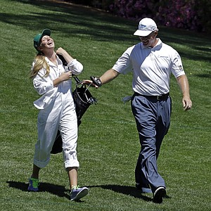 Ernie Els, of South Africa, walks with his daughter Samantha on the third fairway during the Par-3 Contest at Augusta National.
