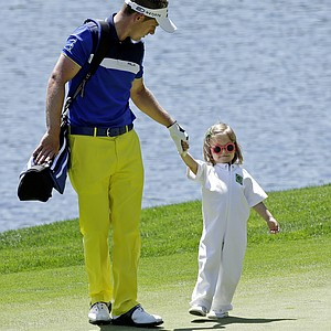 Luke Donald, of England, walks with his daughter on the fourth green during the Par-3 Contest.