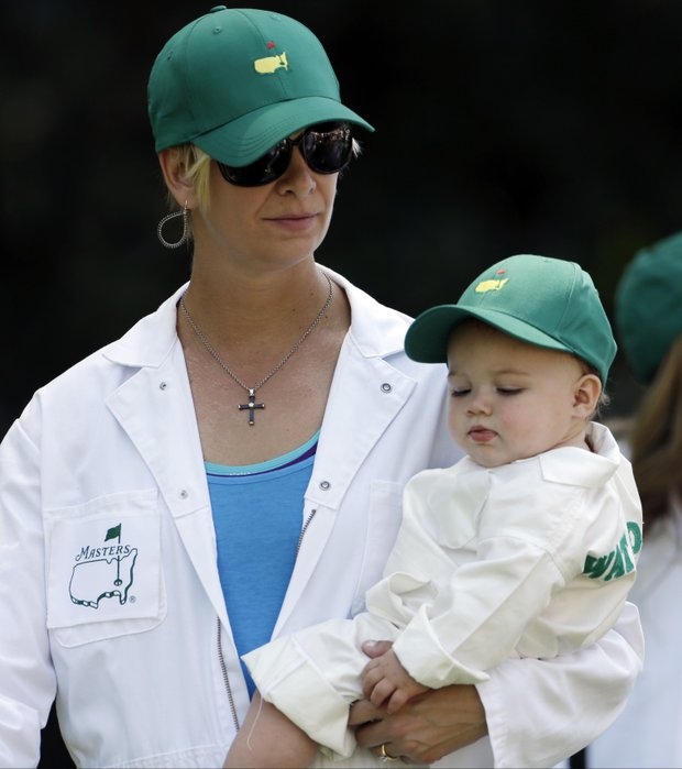 Bubba Watson's wife Angie carries their child, Caleb, during the Masters Par-3 Contest at Augusta National on April 10.