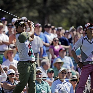 Ryo Ishikawa, right, of Japan, watches as Hiroyuki Fujita, of Japan, tees off on the 12th hole during a practice round for the Masters.