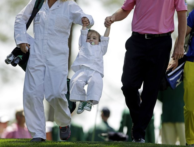 Brandt Snedeker and his wife Mandy lift their daughter Lily during the Par-3 Contest at the Masters.