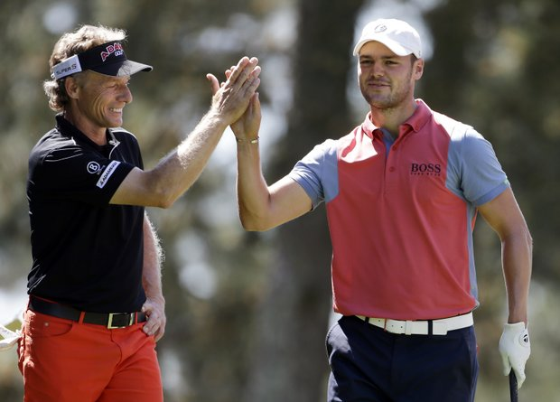 Martin Kaymer, right, of Germany, high fives Bernhard Langer, of Germany, after teeing off on the first hole for a practice round at Augusta National.