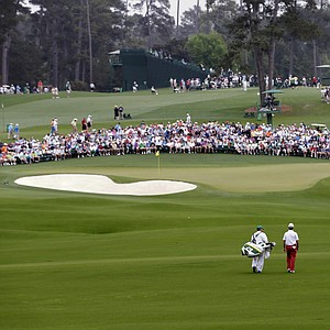 Mike Weir, of Canada, walks with his caddie Danny Sahk to the second hole during the first round of the Masters.