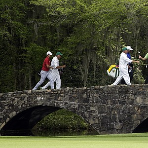 From left, Adam Scott, of Australia, Angel Cabrera, of Argentina, and Sergio Garcia, of Spain, walk across the Nelson Bridget with their caddies during the first round of the Masters golf tournament Thursday.