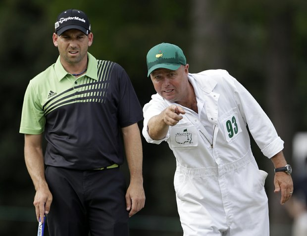 Sergio Garcia, of Spain, listens to his caddie Greg Hearmon on the 14th green during the first round of the Masters golf tournament.