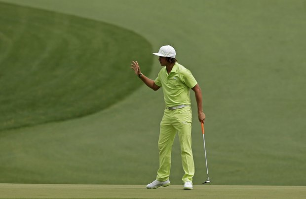 Rickie Fowler waves after an eagle on the 15th hole during the first round of the Masters golf tournament.