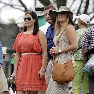 Skier Lindsey Vonn, right, watches Tiger Woods on the ninth hole during the first round of the Masters golf tournament.