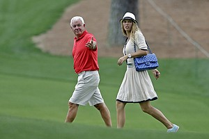 Tennis player Caroline Wozniacki walks with Rory McIlroy's father Gerry during the first round of the Masters golf tournament.