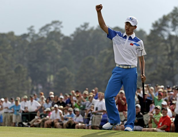 Amateur Guan Tianlang, of China, celebrates after a birdie putt on the 18th green during the first round of the Masters golf tournament.