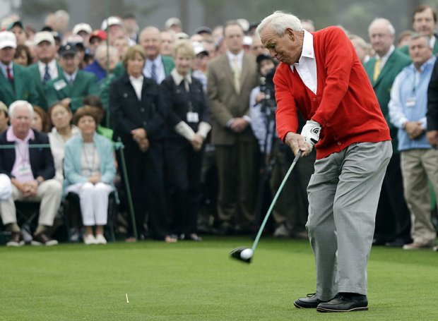 Honorary starter Arnold Palmer hits a ball on the first tee before the first round of the Masters golf tournament.