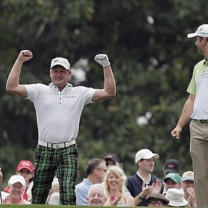 Martin Laird, right, watches as Jamie Donaldson, of Wales, celebrates after Donaldson's hole-in-one from the sixth tee during the first round of the Masters.