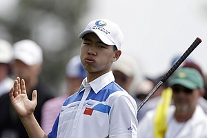 Amateur Guan Tianlang, of China, tees off on the eighth hole during the first round of the Masters.