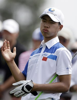 Amateur Tianlang Guan, of China, tees off on the eighth hole during the first round of the Masters.