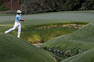 Rickie Fowler hits over Rae's Creek during the second round of the Masters golf tournament.