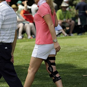 Skier Lindsey Vonn walks through the Augusta National golf course with her leg brace while following Tiger Woods during the second round of the Masters.