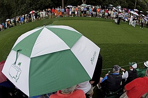 From left, Angel Cabrera, of Argentina, Sergio Garcia, of Spain, and Adam Scott, of Australia, wait to tee off in the rain on the fourth hole during the second round of the Masters.