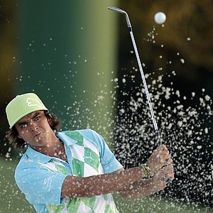 Rickie Fowler hits out of a bunker to the 18th hole during the second round of the Masters golf tournament.