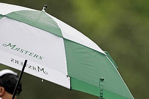 A patron watches rain from under his umbrella at the fourth tee during the second round of the Masters golf tournament.