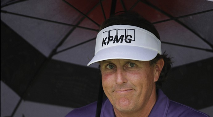 Phil Mickelson takes shelter under an umbrella on No. 2 at Augusta National during the second round of the 2013 Masters, with weather becoming a factor early Friday.
