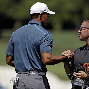 Tiger Woods, left, shakes hands with his swing coach Sean Foley before the third round of the Masters on April 13, 2013, in Augusta, Ga. Woods was assessed a two-stroke penalty by the rules committee for a drop in second round of the Masters.