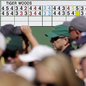 Spectators walk past a leader board displaying Tiger Woods' two first two rounds scores before the third round of the Masters. The score board reflects the 2-stroke penalty assessed to Woods for a drop in 2nd round.