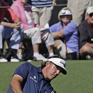 Phil Mickelson chips to the second green during the third round of the Masters.