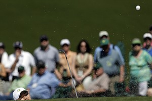Amateur Guan Tianlang, of China, hits out of a bunker on the ninth hole during the third round of the Masters.