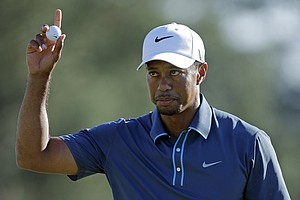 Tiger Woods holds up his ball after putting out on the 18th hole.