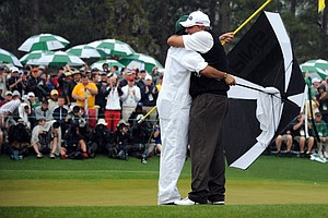 Angel Cabrera hugs his caddie, son Angel Cabrera Jr., after making a birdie putt at No. 18 during the final round of the Masters.