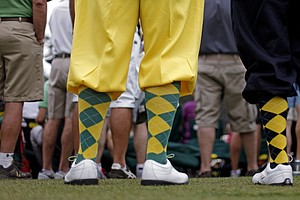 Richard Walker, left, and his son Billy, from Yorkshire, England, wear golf knickers as they watch the fourth round of the Masters.