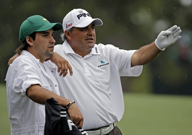 Angel Cabrera, of Argentina, discusses his next shot with his caddie son Angel Cabrera, Jr. on the second hole during the fourth round.