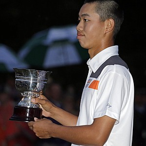 Amateur Guan Tianlang, of China, holds the amateur trophy after the Masters golf tournament.