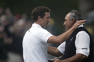 Adam Scott and Angel Cabrera hug at the conclusion of Scott's playoff win in the 2013 Masters.