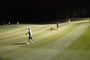 Players attempt to slide down the hill on a par-3 hole during a round of night golf at the Junior Invitational.