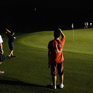 Dylan Wu hits flop shots as Doug Ghim (right) and Robby Shelton watch during a round of night golf on Wednesday night at the Junior Invitational.