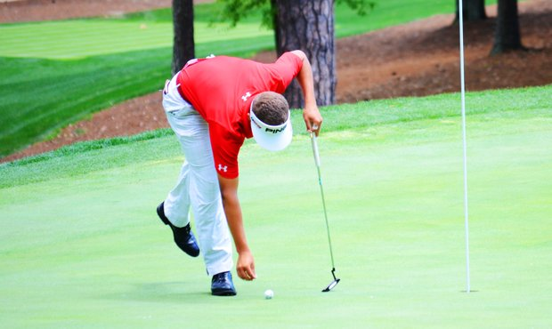 Cameron Champ, of Sacramento, Calif., marks his ball on the 16th green after a stellar tee ball during the junior-am on Thursday at the Junior Invitational at Sage Valley.