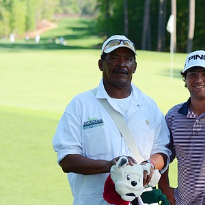 Caddie Bernard Dent, left, and Greyson Sigg take a moment off the back of the 18th green after their junior-am round at the Junior Invitational on Thursday.
