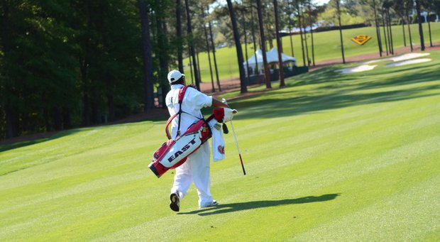 Bernard Dent, who is Greyson Sigg's caddie, walks up the 18th fairway during the junior-am on Thursday at the Junior Invitational.