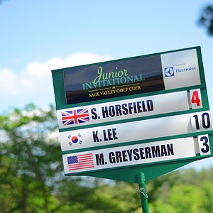 A standard bearer walks off the 18th green after Sam Horsfield fired a 4-under 68 allowed him to take a one-shot lead at the Junior Invitational.