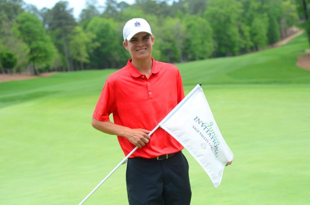Carson Young holds the flag on the 18th green after winning the third annual Junior Invitational at Sage Valley title on Sunday.