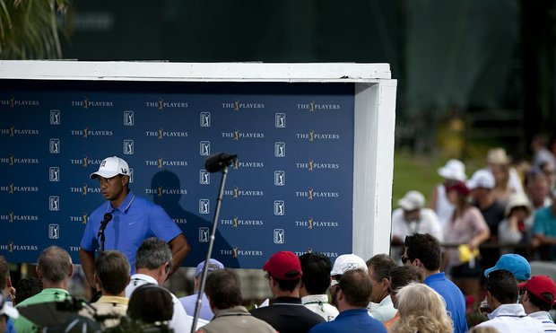 Tiger Woods addresses the media while eager fans wait in the background hoping for an autograph on Tuesday of The Players Championship.