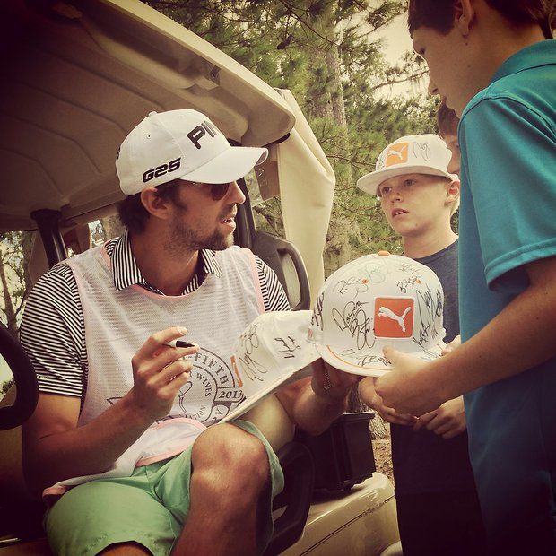 Michael Phelps signs autographs while caddying for Golf Channel's Win McMurry during the PGA Tour Wives Golf Classic on Dye's Valley Course at TPC Sawgrass.