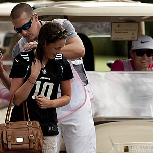 Jacksonville Jaguars kicker Josh Scobee signs an autograph for a fan as Nick Watney comes racing up behind during the PGA Tour Wives Golf Classic.