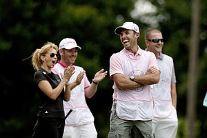 Charl Schwartzel enjoys watching his wife as she stripes the ball down the fairway at No. 3 during the PGA Tour Wives Golf Classic. Behind him is Kate Rose, wife of Justin Rose, Louis Oosthuizen and Jacksonville Jaguars kicker, Josh Scobee.