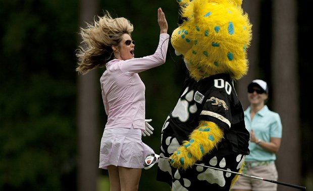 Jim Furyk's wife Tabitha, high-fives Jaxson de Ville of the Jaguars after he hit a drive at No. 3 during the PGA Tour Wives Golf Classic.