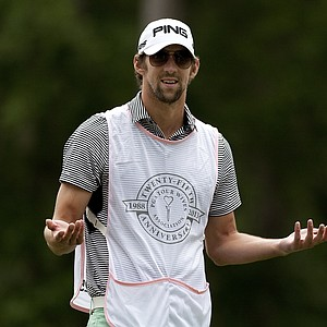 Michael Phelps looks toward Golf Channel's Win McMurry after she hit her drive during the PGA Tour Wives Golf Classic.