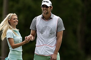 Olympic swimmer Michael Phelps played caddy for Golf Channel's Win McMurry during the PGA Tour Wives Golf Classic.