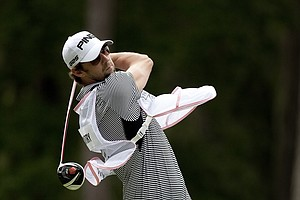 Olympic swimmer Michael Phelps borrows a club to hit a drive on No. 3 during the PGA Tour Wives Golf Classic. Phelps caddied for Win McMurry.