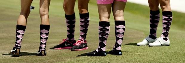 Wives of Matt Bettencourt, Marc Leishman, Aron Price and David Mathis wear coordinated socks during the PGA Tour Wives Golf Classic.