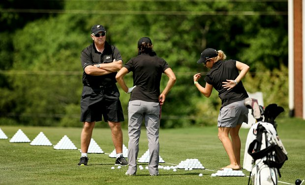 Purdue head coach, Devon Brouse, left, and assistant Caroline Haase, right, work with Paula Reto on the range in Round 2 of the 2013 Women's NCAA Championship.